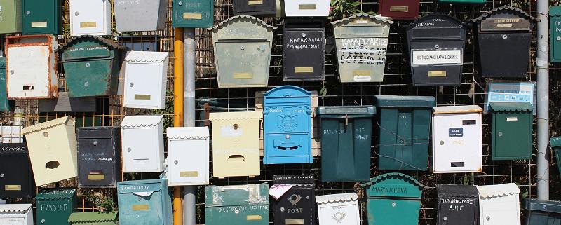 Joukko erilaisia postilaatikoita kiinnitettynä aitaan odottamassa relevantti postia - konversiotavoite suorapostituksessa on oltava maltillinen